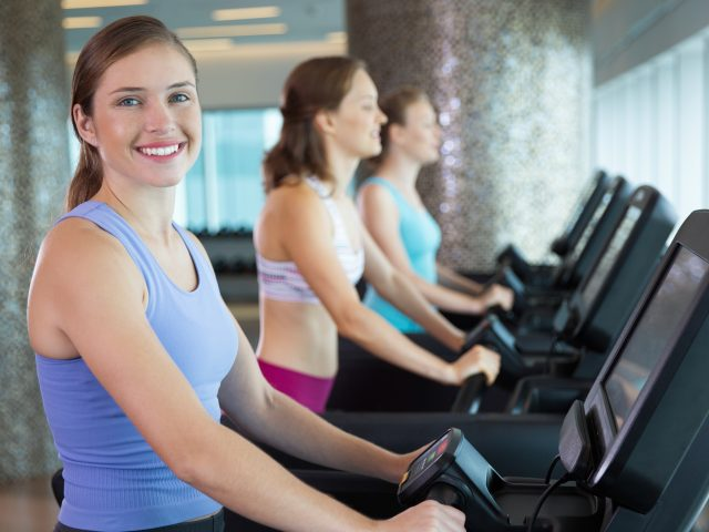 Happy young Caucasian woman wearing sport clothes, exercising on treadmill in gym, smiling at camera. Sporty women running on treadmills in background